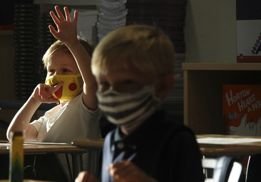 A masked first-grader raises his hand in class.