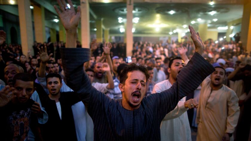 Coptic Christians shout slogans during a funeral service for victims of a bus attack, at Abu Garnous Cathedral in Minya, Egypt, Friday, May 26, 2017.