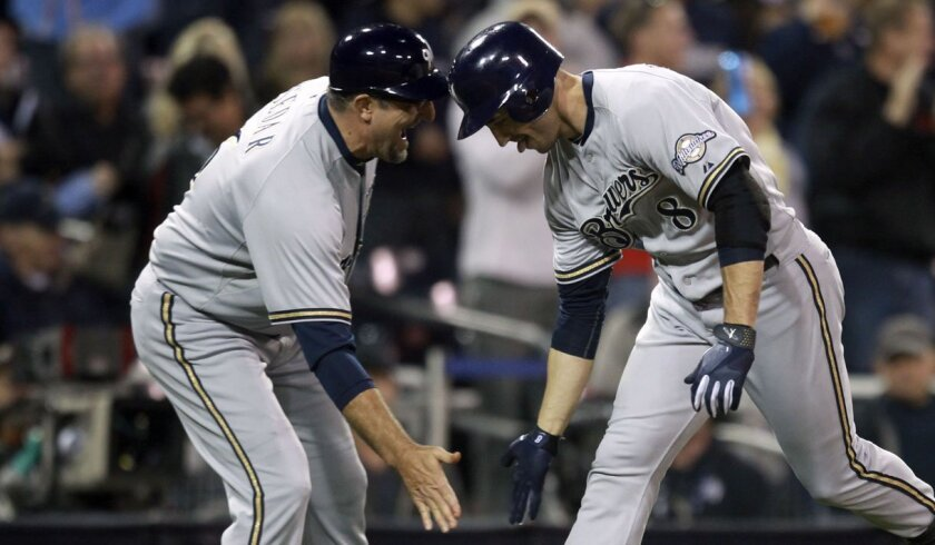 Milwaukee's Ryan Braun low fives third base coach Ed Sedar after Braun's third homer of the night, a record for Petco Park.
