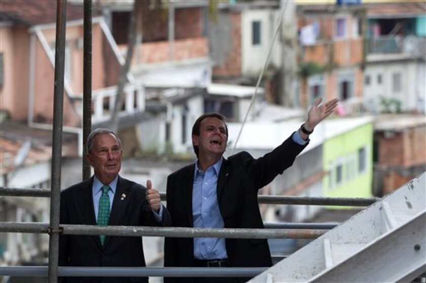 New York Mayor Michael R. Bloomberg, left, and Rio de Janeiro's Mayor Eduardo Paes gesture to construction workers as they visit the Chapeu Mangueira slum during the Rio+C40: Megacity Mayors Taking Action on Climate Change, a parallel event during the UN Conference on Sustainable Development, or Ri
