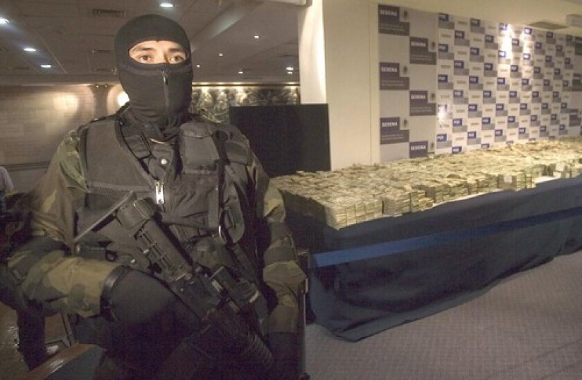 A Mexican army guard stands in front of $26.2 million seized from a house in northwestern Sinaloa state, it was the second largest cash haul in the country's history.