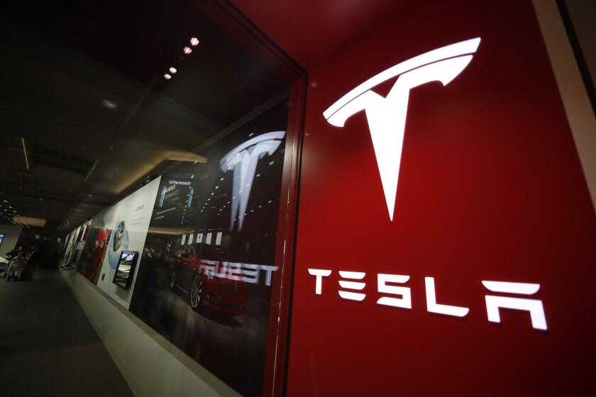 A sign bearing the company logo outside a Tesla store
