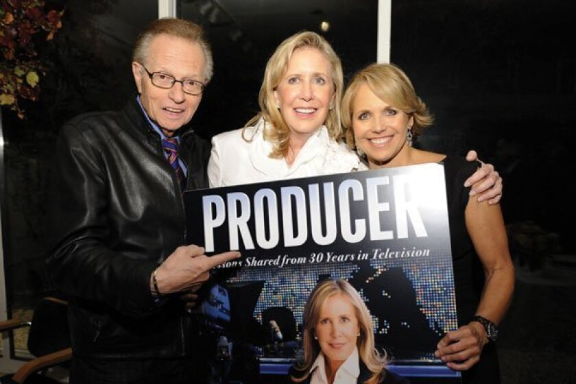 "Wendy Walker (center) holds up a poster of her book, ""Producer: Lessons Shared from 30 Years in Television,"""