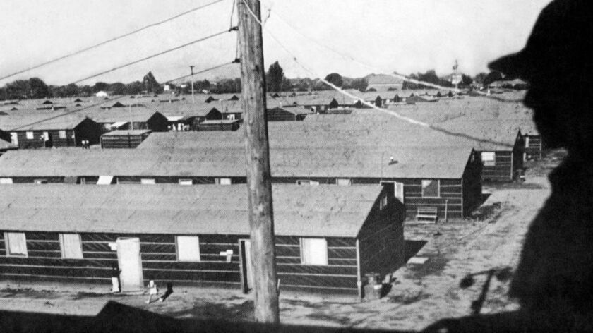 In this undated photo provided by the War Relocation Authority, armed guard overlooks barracks built in the middle of the racetrack at the Fresno Fairgrounds in Fresno. This was the first stop for detainees before they were sent to permanent internment camps.