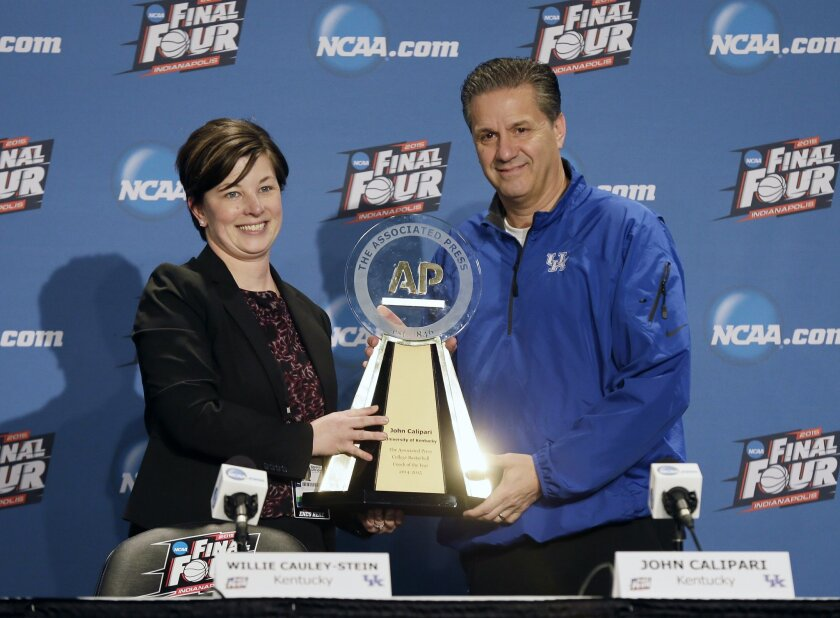 Kentucky head coach John Calipari, right, holds up his AP College Basketball Coach of the Year trophy with Associated Press Deputy Sports Editor Noreen Gillespie at a news conference for the NCAA Final Four tournament college basketball semifinal game Friday, April 3, 2015, in Indianapolis. Kentucky plays Wisconsin on Saturday. (AP Photo/Charlie Neibergall)