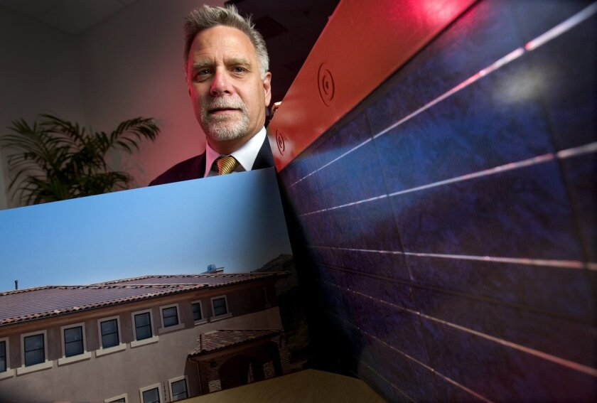 OneRoof Energy CEO David Field holds a solar panel and photo of a building equipped with solar panels. Howard Lipin • UT
