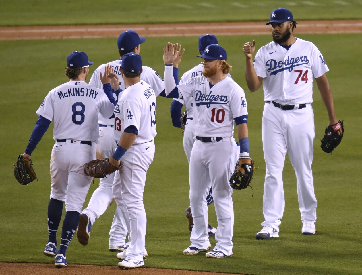 LOS ANGELES, CALIFORNIA - APRIL 14: Justin Turner #10 and Kenley Jansen #74 of the Los Angeles Dodgers celebrate a 4-2 win over the Colorado Rockies with teammates at Dodger Stadium on April 14, 2021 in Los Angeles, California. (Photo by Harry How/Getty Images)