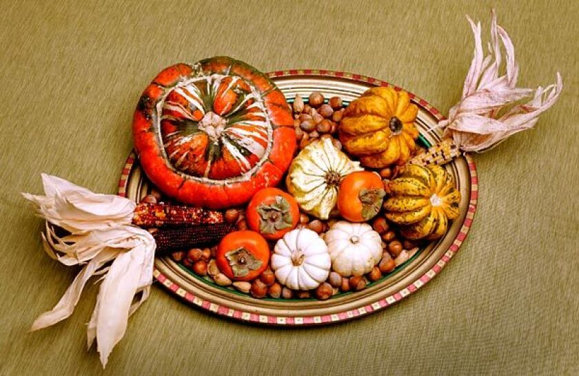 A hand-painted picture frame filled with fruits, vegetables, nuts and dried Indian corn offers a fun twist on the traditional cornucopia.