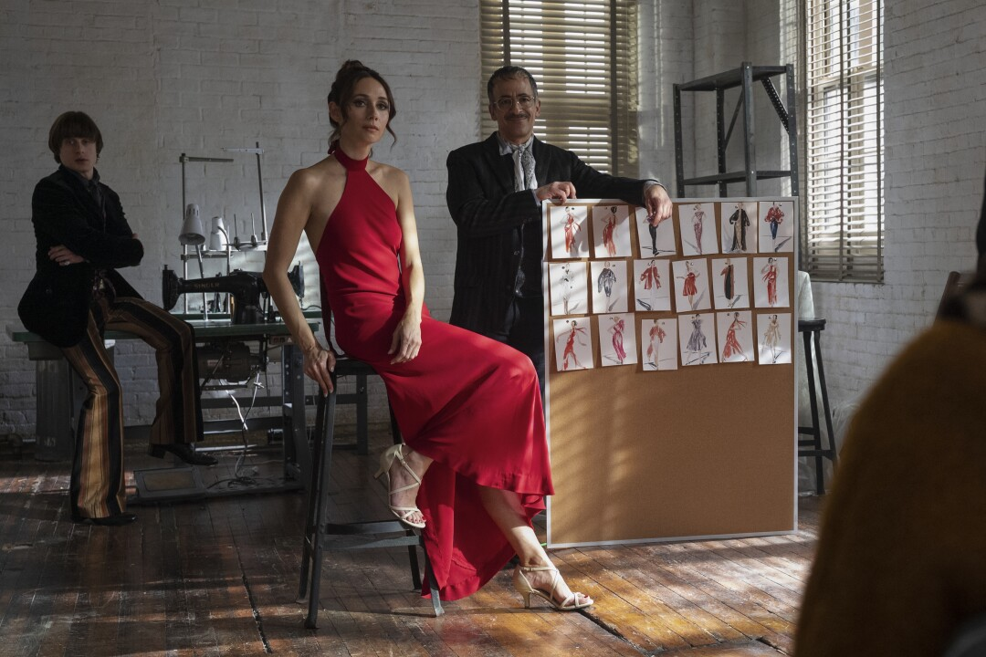 """A woman shows off a crimson halter dress by Halston in a scene from """"Halston."""""""