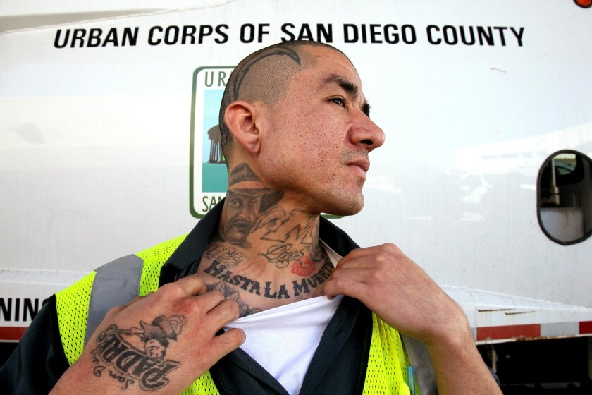 Former gang member Eliseo Nunez displays a few of his many tattoos he got in prison during a break from his job at the Urban Corps of San Diego County recycling center.