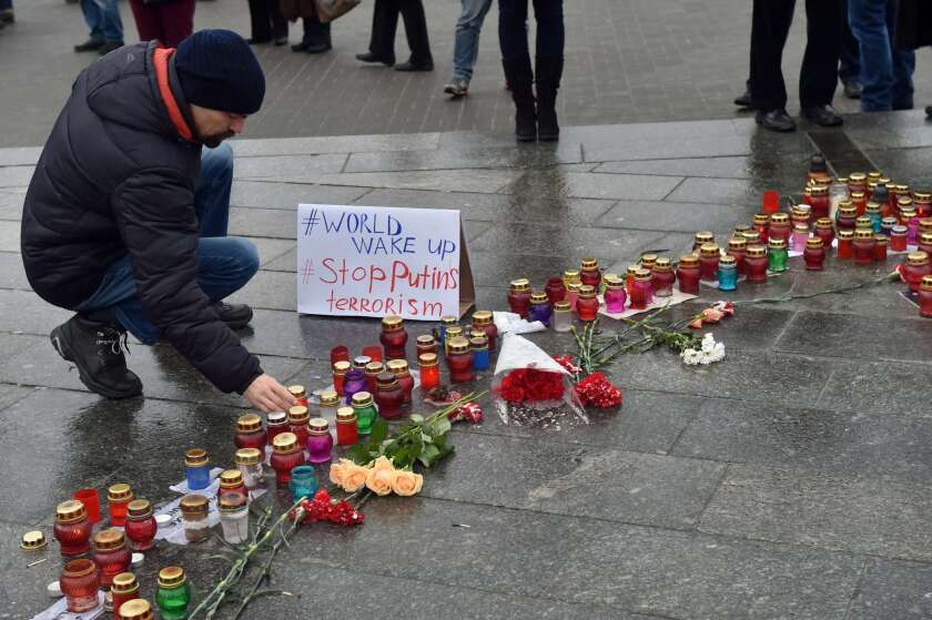 "A man sets a candle near placard reading ""World wake up. Stop Putin's terrorism"" on Independence Square in Kiev, during a rally for people who died as a result of shelling in the southern Ukrainian city of Mariupol."