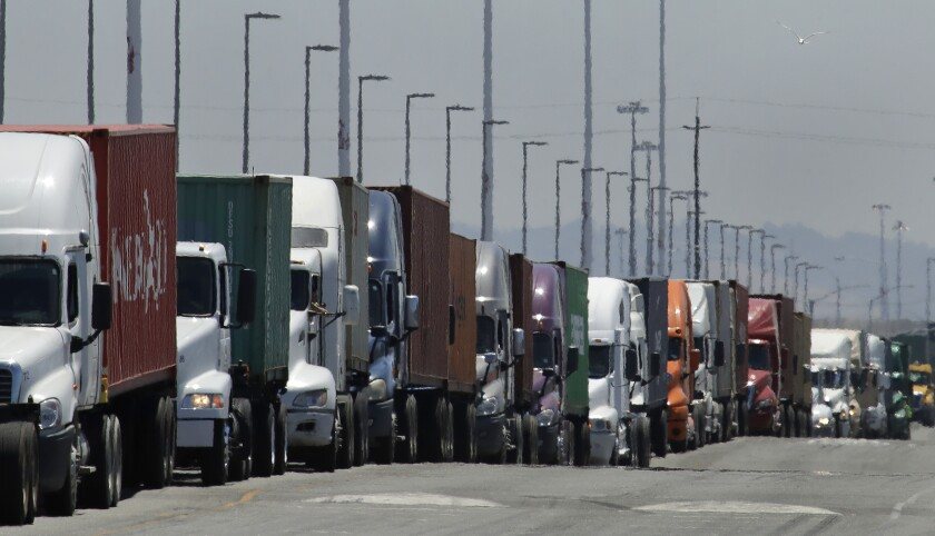 Trucks are hauling shipping containers.