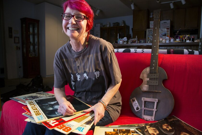 Sandi Weller, who was 10 when she attended the Beatles concert at Balboa Stadium in 1965. Next to her is a replica of Paul McCartney's bass that her father made.