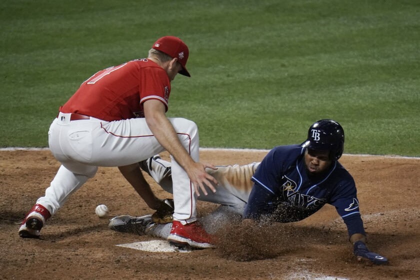Tampa Bay Rays' Manuel Margot steals home to score as Angels pitcher Aaron Slegers misses the throw.
