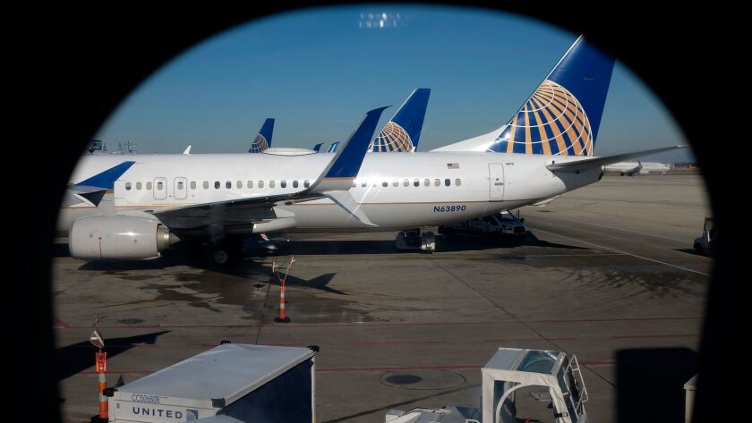 In this Nov. 22, 2017, photo taken through an aircraft passenger window, United Airlines planes are