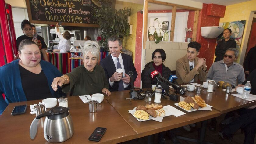 San Ysidro resident Luz Camacho Espinoza reached for coffee to serve Gov. Gavin Newsom at the El Rincon restaurant in San Ysidro where he met with a small group of community representatives on Thursday to listen to their concerns about their border community.
