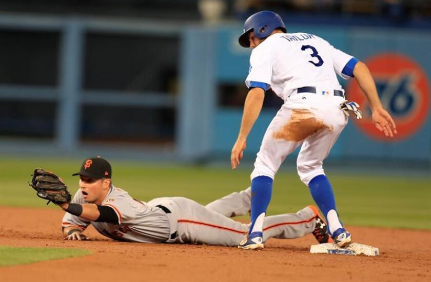 El jugador Chris Taylor (d) de los Dodgers de Los Ángeles llega a segunda base ante Joe Panik (i) de los Gigantes durante un partido. EFE/Archivo