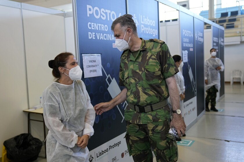 Rear Admiral Henrique Gouveia e Melo shares a joke with a military nurse during a visit to a vaccination center in Lisbon, Tuesday, Sept. 21, 2021. As Portugal nears its goal of fully vaccinating 85% of the population against COVID-19 in nine months, other countries want to know how it was able to accomplish the feat. A lot of the credit is going to Gouveia e Melo. (AP Photo/Armando Franca)