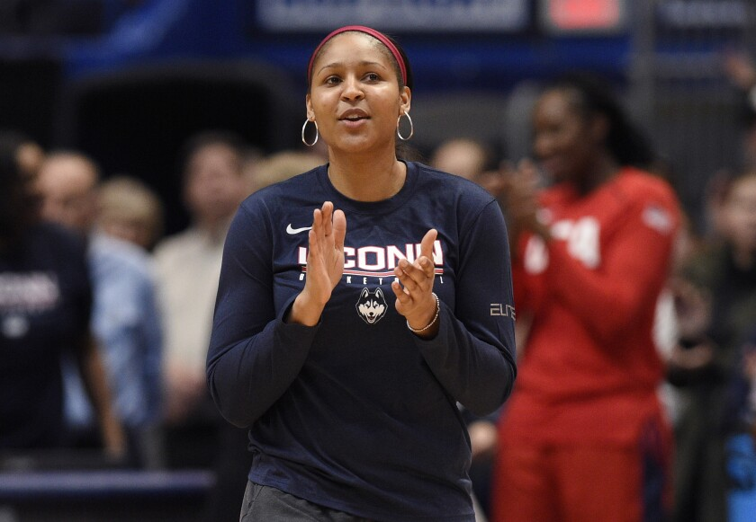 FILE - In this Jan. 27, 2020, file photo, former Connecticut and Minnesota Lynx player Maya Moore applauds in Hartford, Conn. Moore says she is not ready to return to the WNBA. The basketball star said on ABC's Good Morning America that she remains focused for now on her marriage to Jonathan Irons and their activism for criminal justice reform. She has not played for the Minnesota Lynx since the 2018 season. (AP Photo/Jessica Hill, File)