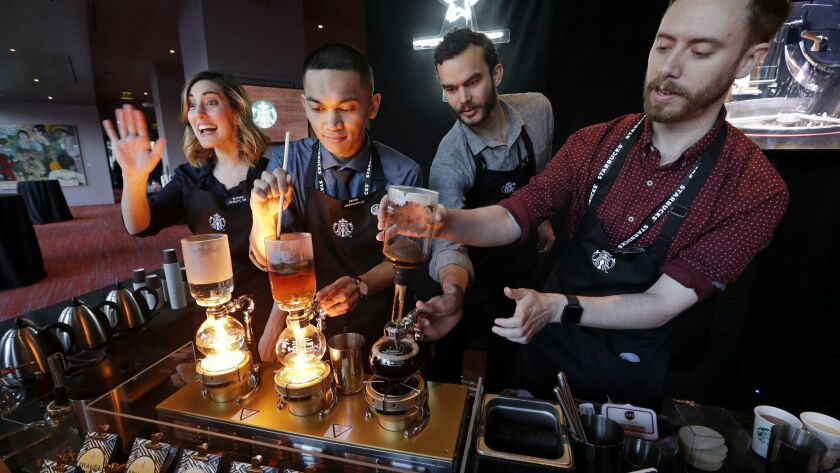 Baristas from Starbucks' specialized coffee shop, Reserve Roastery, demonstrate a siphon brew of individual cups of coffee.