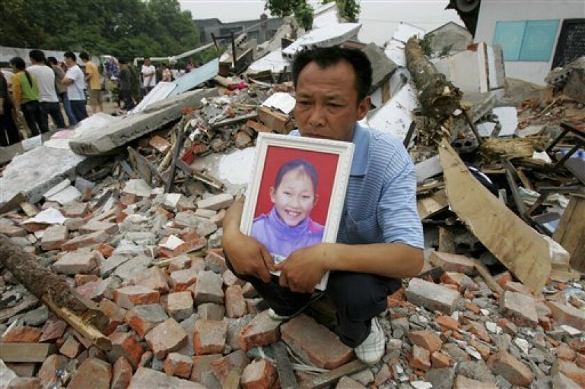 FILE - In this May 23, 2008 file photo, a father holds a photo of his daughter who was killed in an earthquake, while sitting in the ruins of the Fuxin No. 2 Primary School in Wufu, in China's southwest Sichuan province. On Thursday, May 7, 2009, China says that 5,335 students died in last year's Sichuan earthquake, the first time a number had been given for the politically charged issue. (AP Photo/Greg Baker, File)