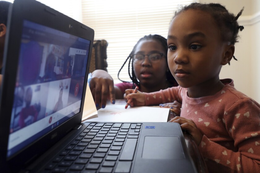 Lear Preston, 4, attends her Scott Joplin Elementary School virtual classes as her mother, Brittany Preston, background, assists at their residence in Chicago's South Side, Wednesday, Feb. 10, 2021. Starting Thursday, Lear will return to class as the nation's third-largest school district slowly reopens its doors following a bitter fight with the teachers union over COVID-19 safety protocols. (AP Photo/Shafkat Anowar)