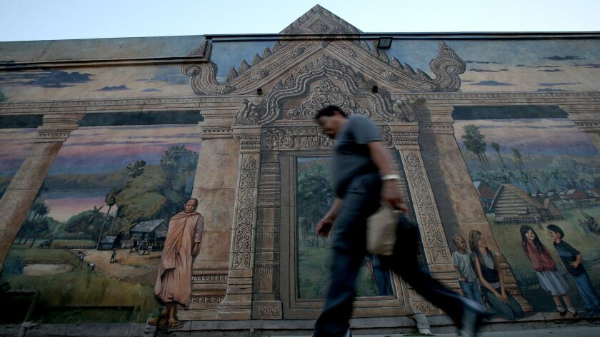 LONG BEACH, CALIF. - JULY 14, 2017. A man walks past a mural depicting the life of Cambodians just