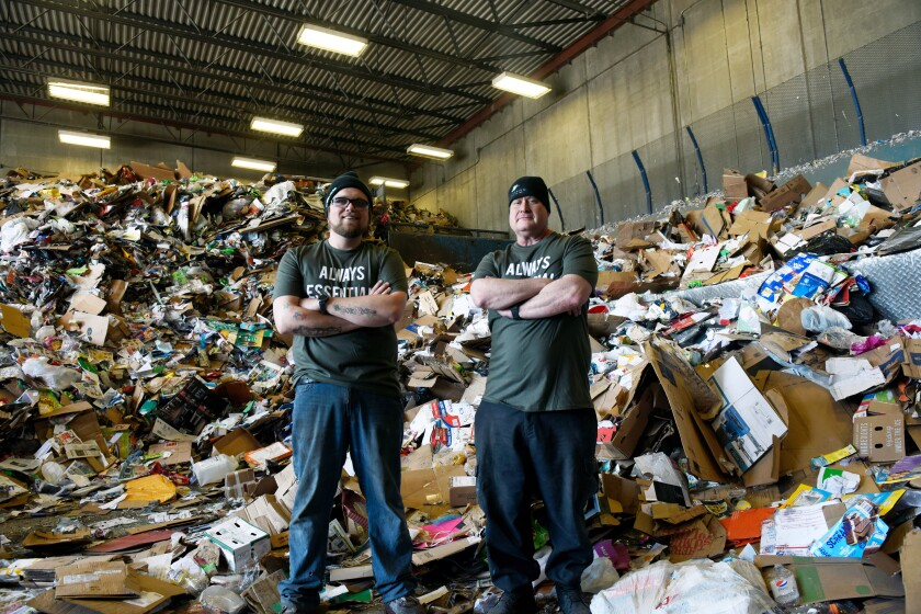 Nate Riddle and Tim Kachel stand at the recycling plant where they found Parker Hanson's prosthetic arm on Tuesday, May 11, 2021, in Sioux Falls, S.D. Hanson, a college baseball player from South Dakota, prosthetic arm was stolen from his vehicle when discovered his backpack missing on May 3 and took to social media to vent his frustrations. The next day the Sioux Falls Police Department recovered a backpack with some of the prosthetic's attachments near Hanson's house. (Alfonzo Galvan/The Argus Leader via AP)