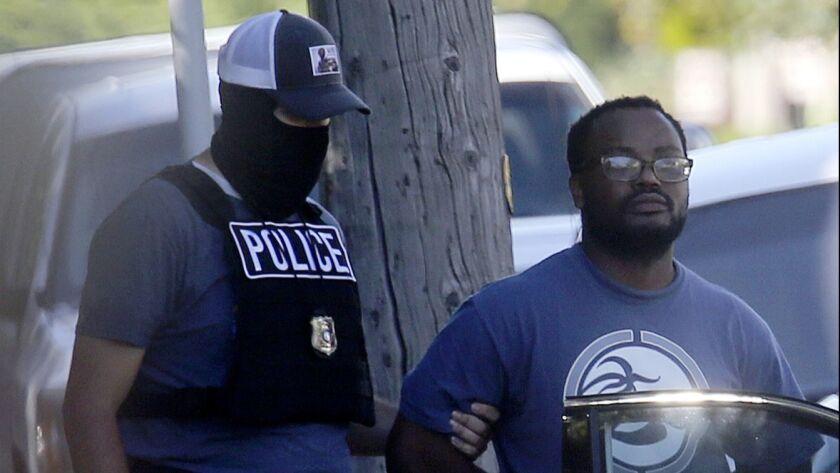 Salt Lake City police take Ayoola A. Ajayi into custody.