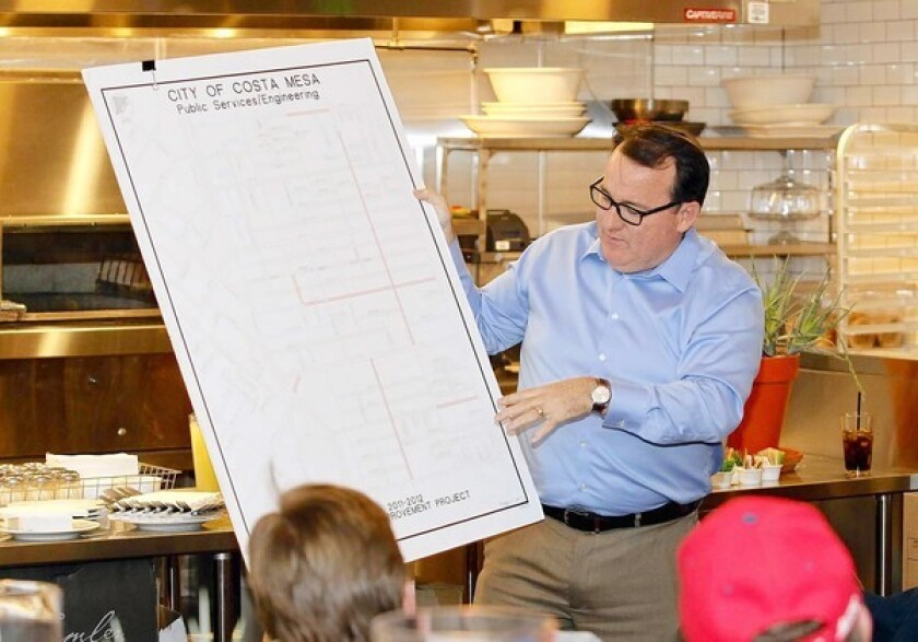 Mayor Jim Righeimer holds up and shows a Costa Mesa street improvement map during Meet the Mayor session at Pitfire Artisan Pizza on Thursday.