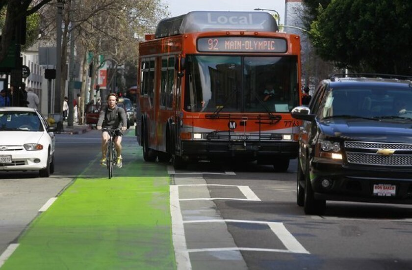 Cyclists, cars and buses pass on the green-painted bike lane in the 400 block of Spring Street in Los Angeles.