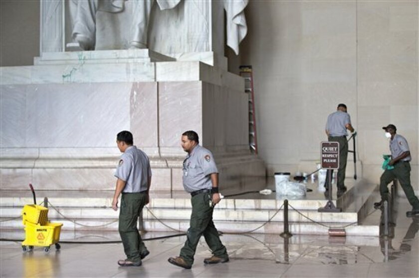FILE - This July 26, 2013 file photo shows National Park Service workers cleaning the Lincoln Memorial in Washington, after someone splattered green paint on the statue of the 16th president and the floor area. National Park Service officials say three areas of the Lincoln Memorial statue still show faint signs of green staining after a vandal splattered green paint at the site last week. (AP Photo/J. Scott Applewhite, File)