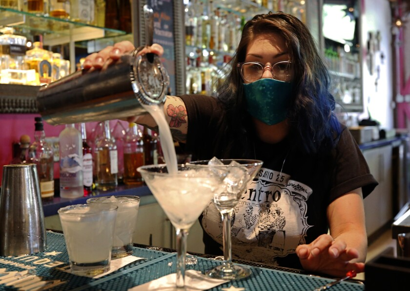 Bartender Taylor Osorio wears a face mask as she pours drinks at Centro Cocina Mexicana restaurant in Sacramento on Friday. A state rule change will make it easier for bars and wineries to sell to-go drinks.