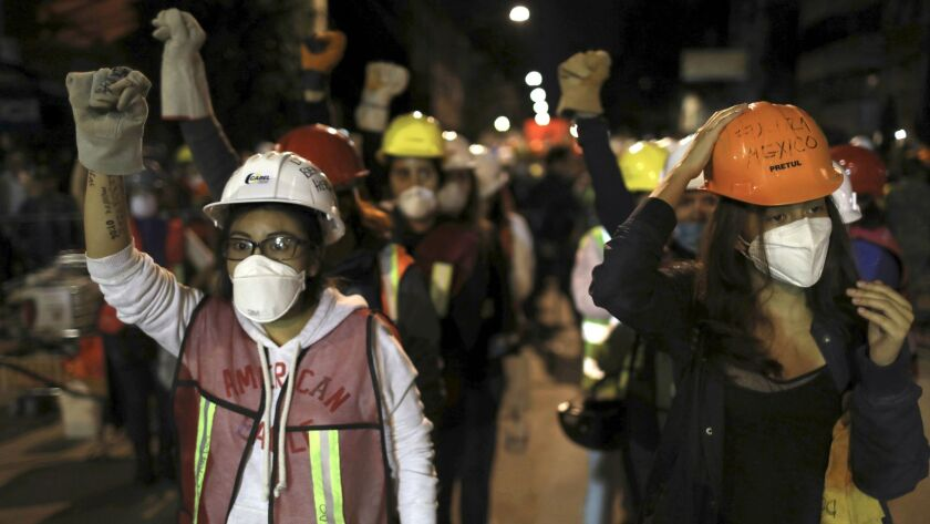 Volunteers gear up at a search and rescue site in Mexico City early Sunday.