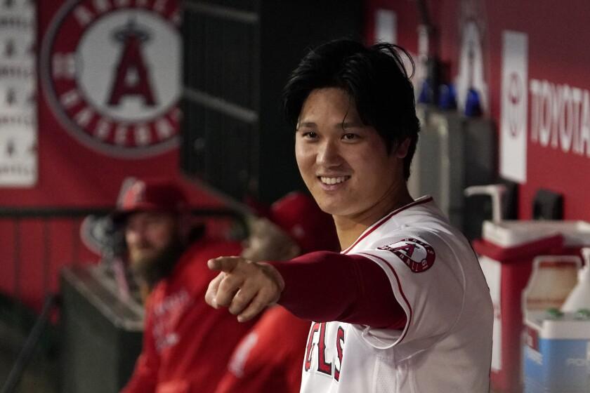 Shohei Ohtani, de los Angelinos de Los Ángeles, gesticula hacia otros jugadores en la banca.
