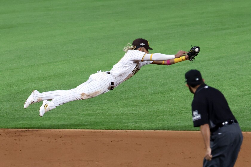 Fernando Tatis Jr. #23 of the San Diego Padres dives to cut off a ball.