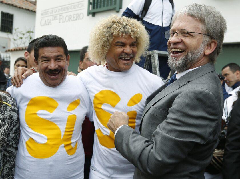 El ex futbolista Carlos Valderrama, en el centro, el ex boxeador Miguel Lora, a la izquierda, y el ex candidato a la presidencia Atanas Mockus, a la derecha, ríen durante un acto organizado por partidarios de un acuerdo de paz con las Fuerzas Armadas Revolucionarias de Colombia, o FARC, el miércoles 7 de septiembre de 2016. (AP Foto/Fernando Vergara, Archivo)