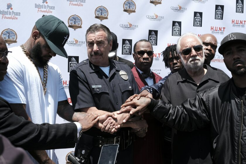 """Los Angeles Police Chief Charlie Beck, middle, holds hands with The Game, left, and Nation of Islam minister Tony Mohammed, right, wearing a bow tie, and other community leaders during """"Time To Unite: United Hoods + Gangs Nation,"""" a community summit organized by rappers The Game and Snoop Dogg, in South Los Angeles with local gang members to discuss ways to curb violence, at the Church of Scientology Community Center, Sunday, July 17, 2016. (AP Photo/Richard Vogel)"""