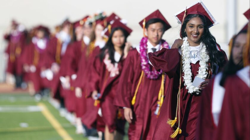 Graduating senior Rucha Kadam smiles as she walks with her class into the graduation ceremony for La