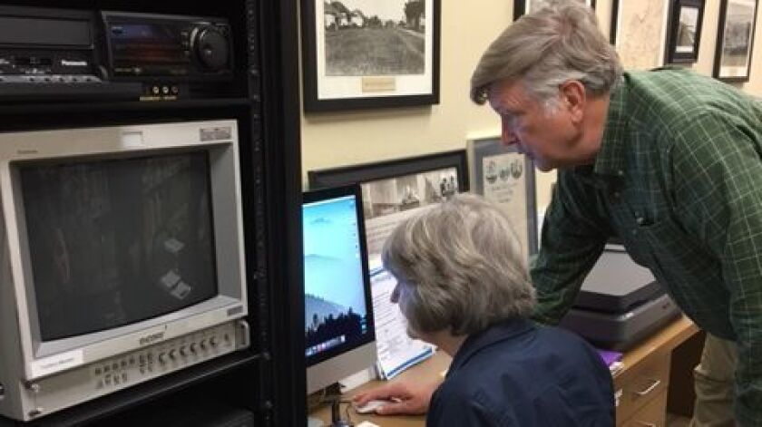 Volunteer Darryl Templer helps a patron digitize her photos at the Memory Lab opening.