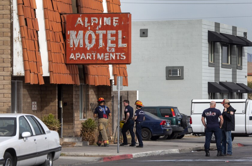Firefighters outside of a building with a red sign that reads Alpine Motel Apartments.