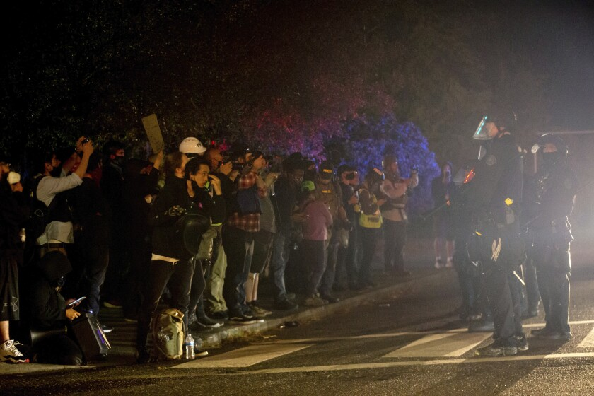 Demonstrators gathered at Floyd Light City Park on Thursday, Aug. 6, 2020 in Portland, Ore. Protests turned violent again even after the mayor pleaded with demonstrators to stay off the streets. Police say an officer suffered what was described as a severe injury after being hit with a rock late Thursday. (Mark Graves /The Oregonian via AP)