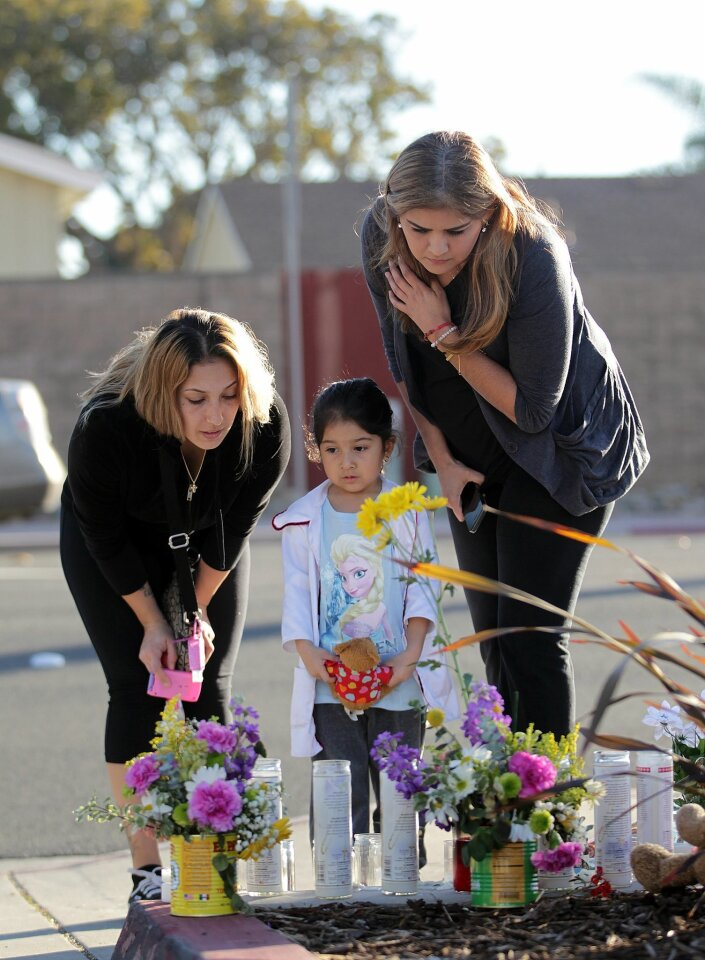 Jessica Krivasich, left, her daughter Sophia Krivasich, 3, and Jessica's sister-in-law Anamaria Leal, who all live around the corner from the crime scene, pay their respects to baby Eliza Delacruz Monday afternoon.