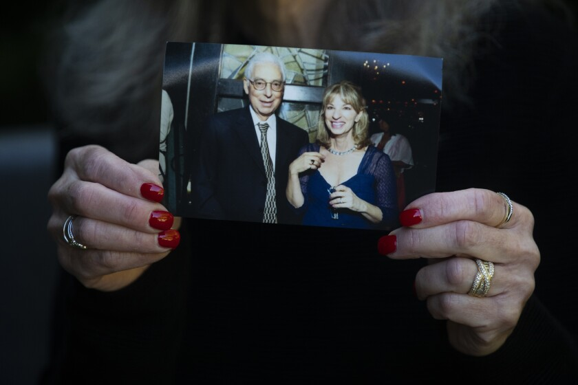 A close-up of a woman's hands holding a photo of her brother and sister