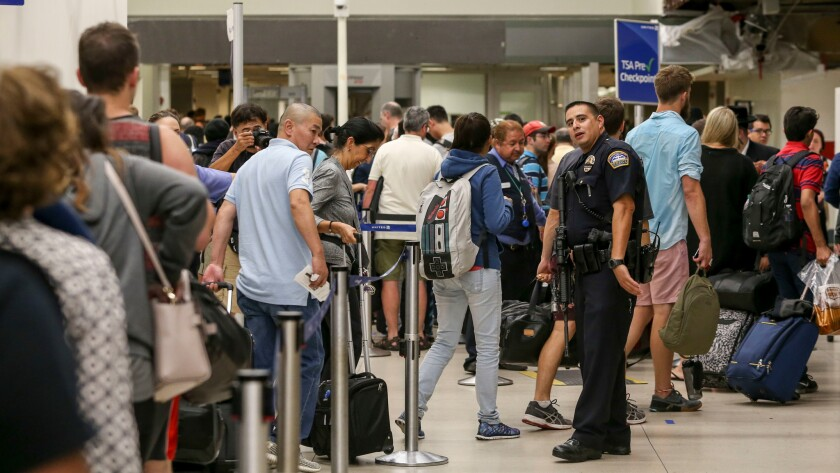 A police officer stands guard while passengers wait in line to be re-screened at Los Angeles International Airport on Aug. 28, after a false report of a gunman opening fire caused people to flee the terminals.