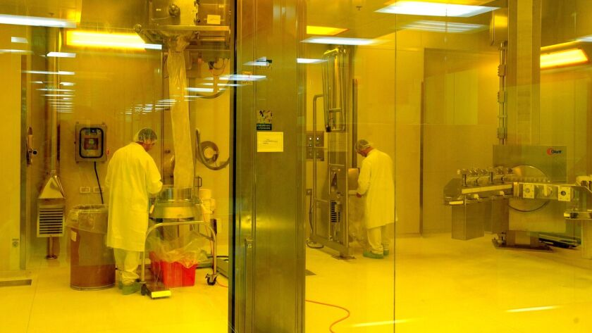 Workers check pharmaceutical products during the production process at Teva Pharmaceutical Industrie