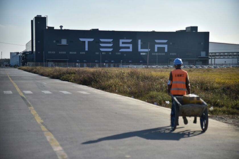 A worker walks on a road next to the new Tesla factory built in Shanghai.