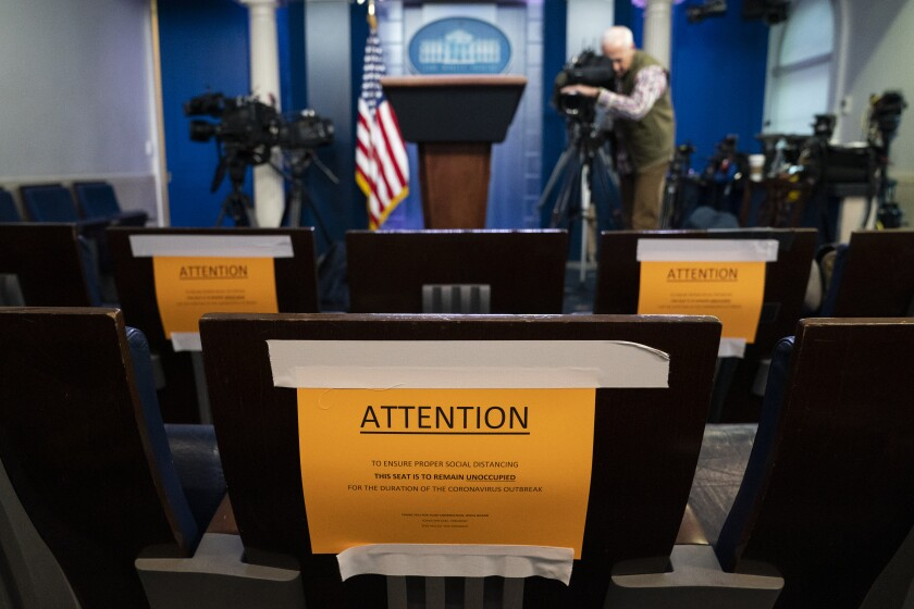 Signs in the briefing room of the White House indicate social distancing measures being taken to separate reporters working at the White House, Monday, March 16, 2020, in Washington. (AP Photo/Evan Vucci)