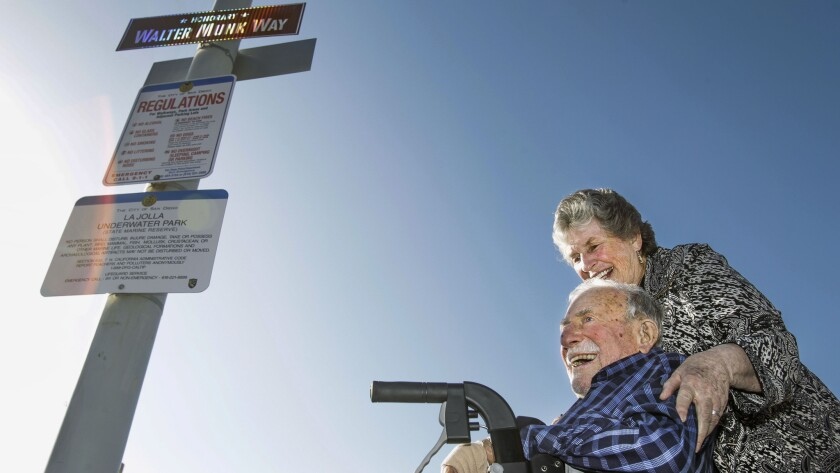 """Mary Munk stands next to her husband the legendary oceanographer Walter Munk just after the unveiling of the """"Walter Munk Way"""" sign, upper left, Wednesday on the La Jolla Shores boardwalk. Munk turns 100-years-old Thursday."""