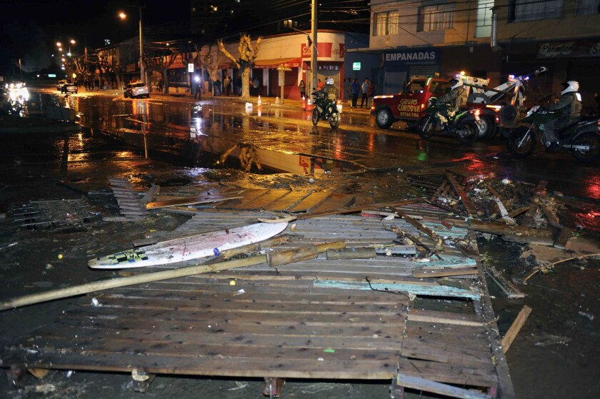 Police patrol a debris-strewn street in Valparaiso, Chile, after a tsunami hit the area following a massive earthquake on Sept. 16.